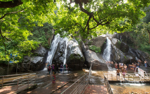 Men gather to bathe under the cool water of the five falls waterfalls in Kutralam