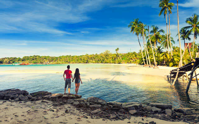 A loving couple enjoying the breathtaking views of the tropical sandy beach with green coconut palm trees and beautiful clean sea ocean on a background of blue sky in goa