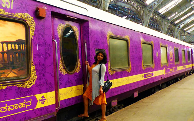 A young lady posing near the Golden Chariot train