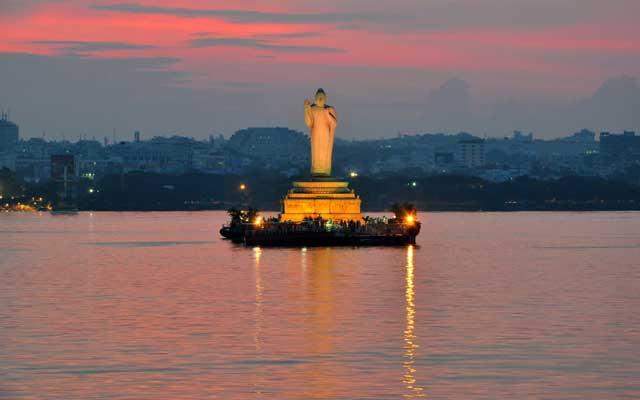 Buddha statue at dusk in Hussain Sagar in Hyderabad, India.