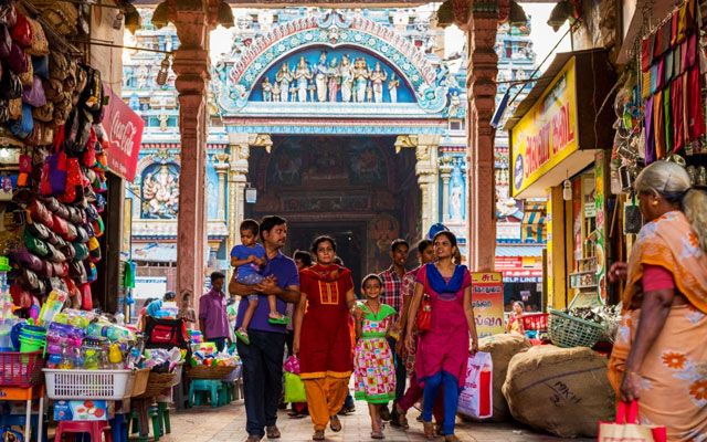 An Indian family walks through an arch occupied by shops, with famous Meenakshi Temple (also known as Meenakshi Amman or Meenakshi-Sundareshwara Temple) in the background.