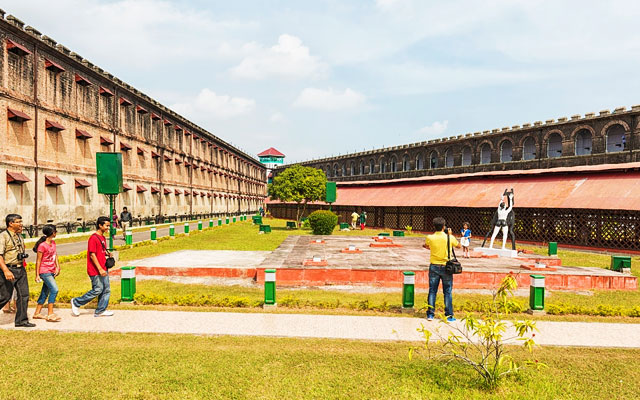Small group of tourists walking on path and taking photos in Cellular Jail at Port Blair in Andaman and Nicobar Islands