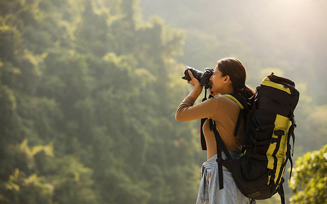 A young Indian women traveler taking photos with camera in Chikmagalur hills.