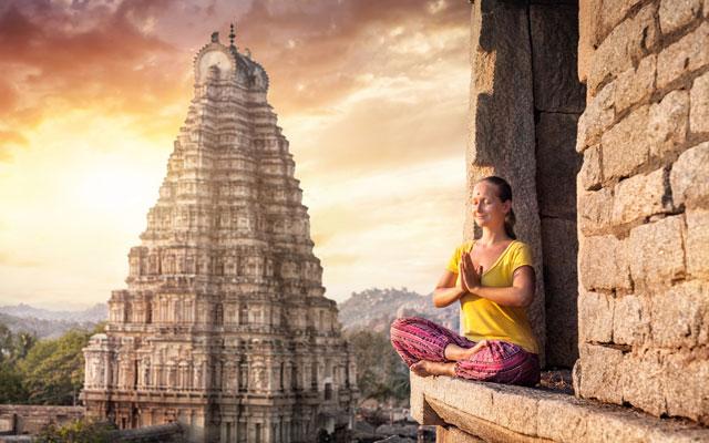 Woman with Namaste mudra sitting near Virupaksha temple in Hampi, Karnataka, India