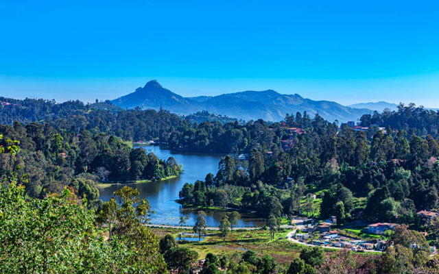 Looking Down At Kodaikanal Lake From A Higher Elevation In The Colonial Town In The State Of Tamil Nadu; In The Far Background Is The Peak Known Locally As Perumal Malai.