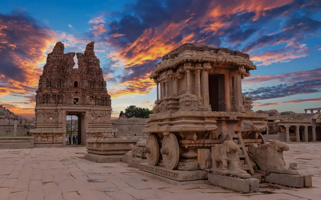 Ancient Hampi Monument Stone Chariot in the the Vittala Temple Complex with dramatic skies during sunset in Unesco Heritage Hampi town Karnataka