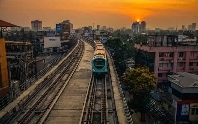 A scenic view of metro train in Kochi running through the tracks during evening.