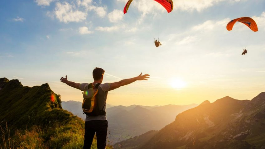 man on a hike in the mountains at sunset with paraglider in background